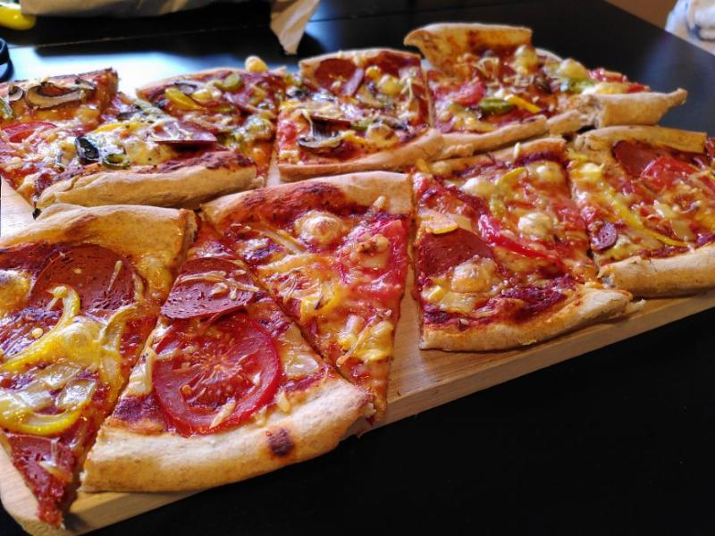 A rectangular bamboo chopping board with 16 slices from two pizzas on top.  Front row is a simple vegan pepperoni with three 'cheeses' and the back row is the same but with jalapenos and mushrooms.